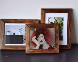 Three small wooden frames. Io one of them is an illustrated female portrait by Darka White. In two others are photos of some plants.