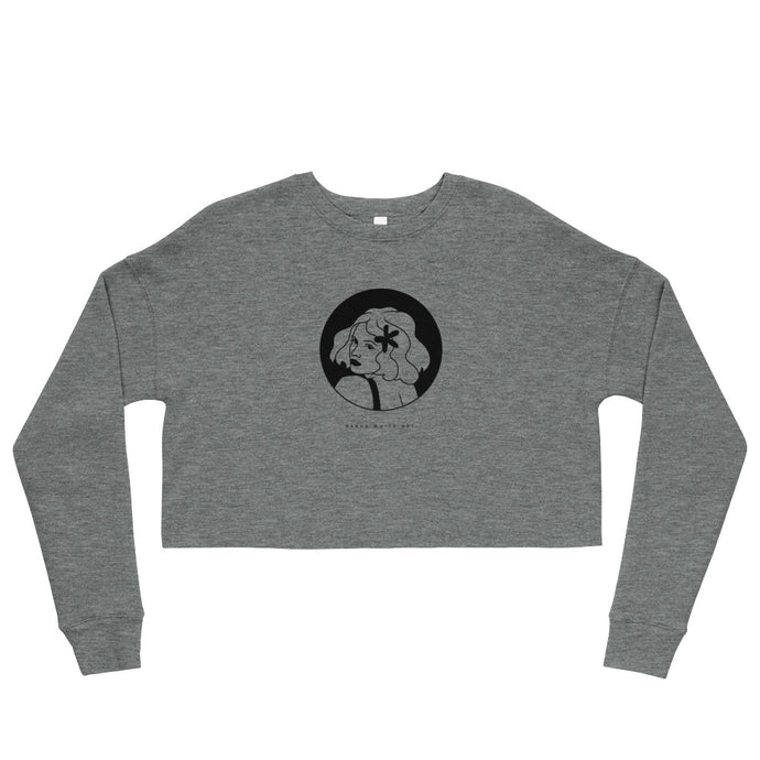A gray crop sweatshirt with a print. The print is a circled illustration of a woman's portrait. A sign says: