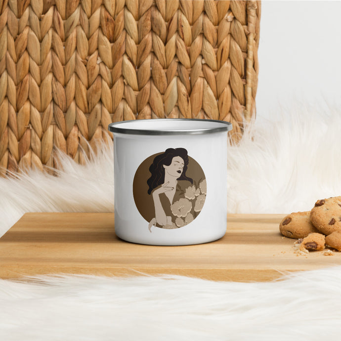 An enamel mug with a female portrait illustrated by Darka White. Mug is on a wooden desk, next to it are chocolate cookies.