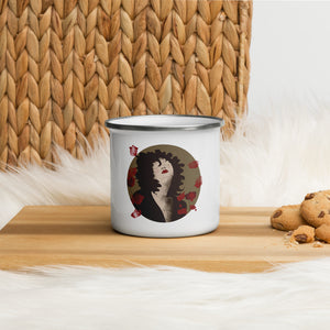 An enamel mug with an illustrated female portrait by Darka White. Mug is on a wooden desk, next to it are chocolate cookies .