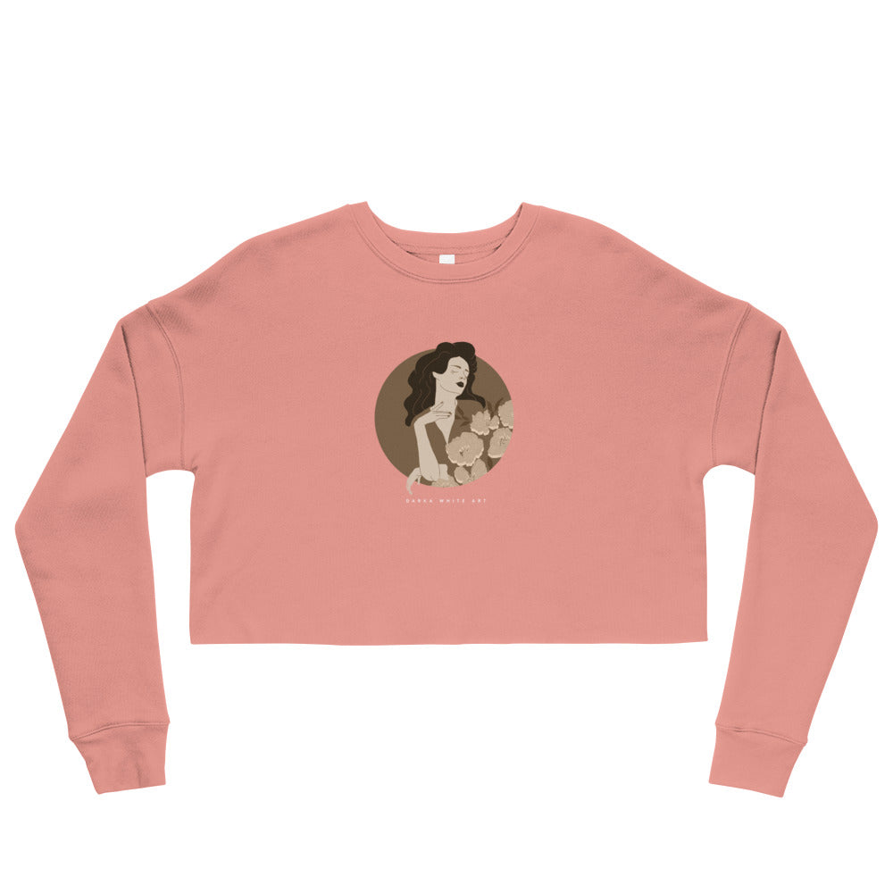 A pink crop sweatshirt with a print. The print is a circled illustration of a woman's portrait. A sign says: