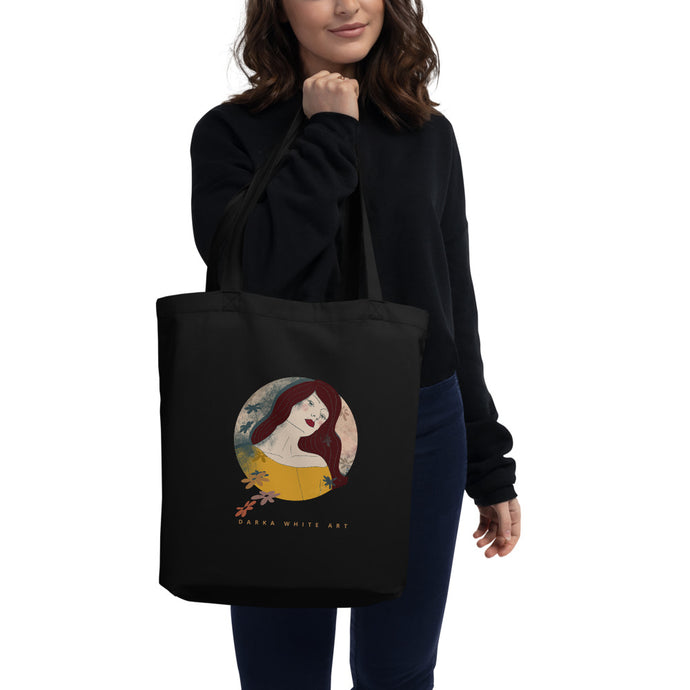 A girl holding a tote bag in her hand. There's a beautiful illustrated art print of a woman's portrait on the bag and a sign