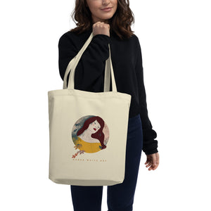 "A girl holding a tote bag in her hand. There's a beautiful illustrated art print of a woman's portrait on the bag and a sign ""Darka White Art"""