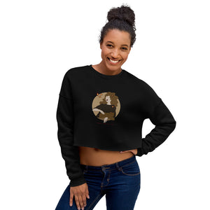 "A woman wearing a crop sweatshirt with a print. The print is a circled illustration of a woman's portrait. A sign says: ""Darka White Art"""