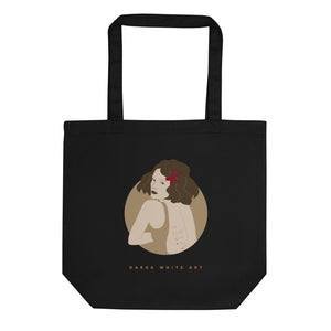 "A black tote bag with a beautiful illustrated art print of a woman's portrait and a sign ""Darka White Art"""