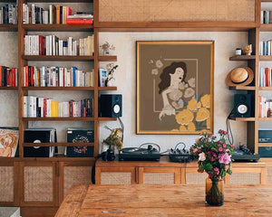 A framed illustrated female portrait (created by Darka White). The frame is on the wall, around are wooden shelves with books, In front is a table  with a vase and some flowers in it.