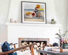 Load image into Gallery viewer, A framed illustration of two women resting by the sea, created by Darka White. The frame is on a shelf above the chimney in a living room.