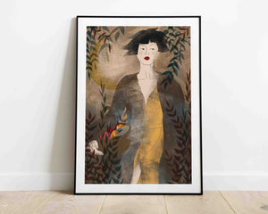 A framed stylized illustrated female portrait with a basket of fruit and a moon behind her. Created by Darka White. The frame is on the floor, leaning on the wall.