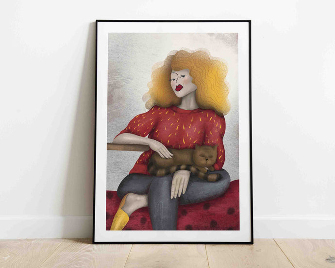 A framed stylized illustrated artwork of a woman with a cat. Artwork is by Darka White. The frame is on the floor, leaning on the wall.