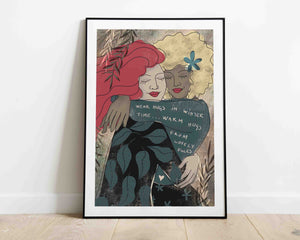 "A framed stylized illustration of two women hugging. One of them is wearing a sweater with a sign: ""Wear hugs in winter time, warm hugs from lovely folks."" The artwork is by Darka White. The frame is on the floor, leaning on the wall."