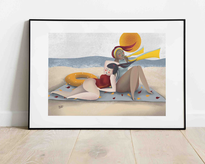 A framed illustration of two women resting on a towel by the sea, their hair is floating in the wind. Artwork created by Darka White. The frame is on the floor, leaning on the wall.