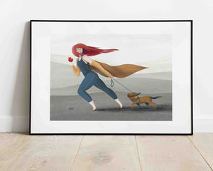 A framed illustration of a girl holding an apple in one hand and a dog on a leash in the other. She's walking outside, it's windy. Illustration by Darka White. The frame is on the floor, leaning on the wall.