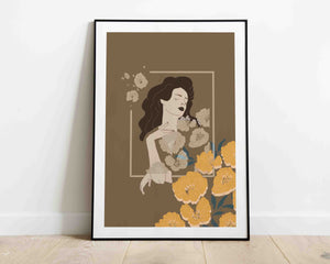 A framed stylized illustrated artwork of a female portrait with  flowers by Darka White.  Frame is on the floor, leaning on the wall.