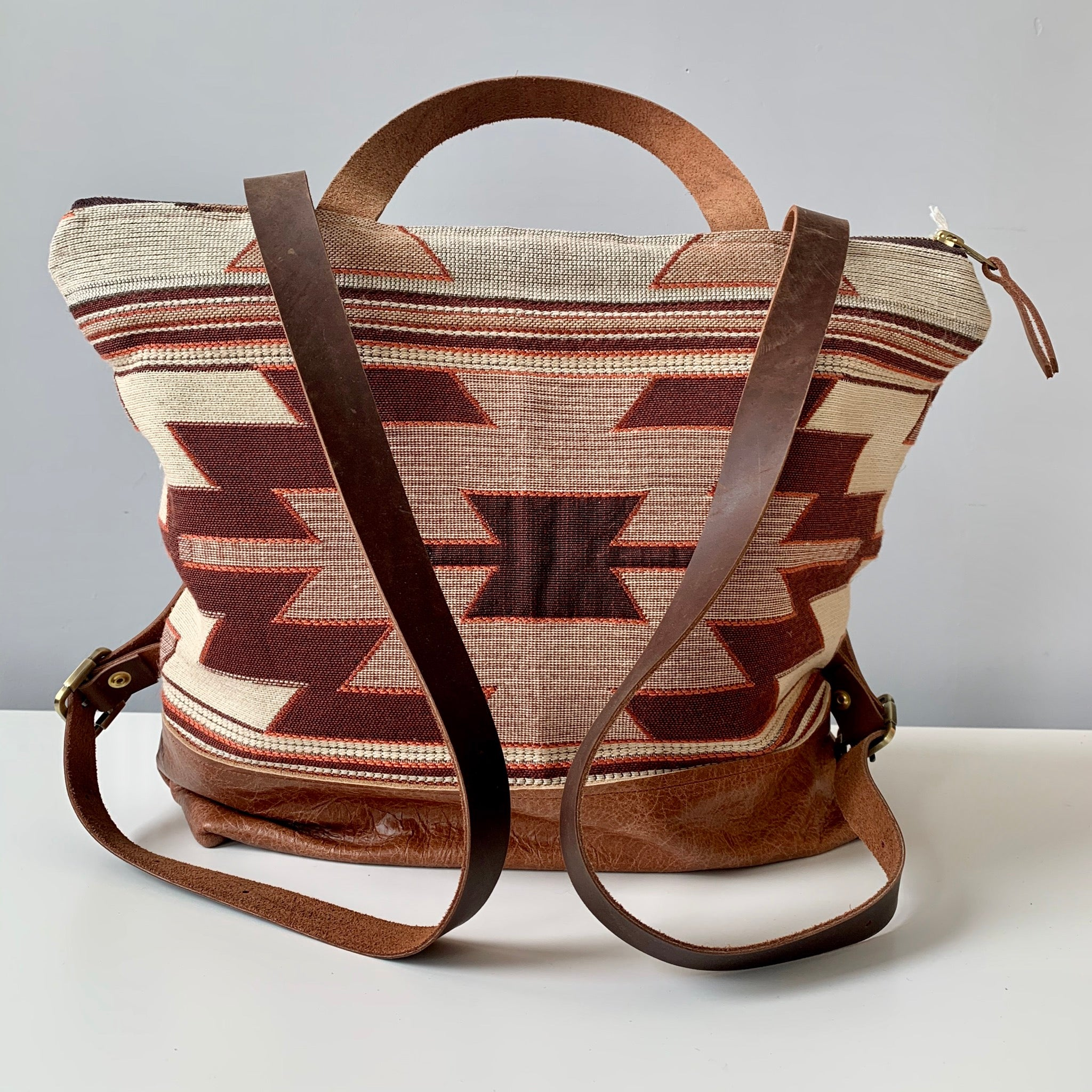 Made in Canada brown leather backpack purse with burgundy, red and beige southwestern patterned fabric.
