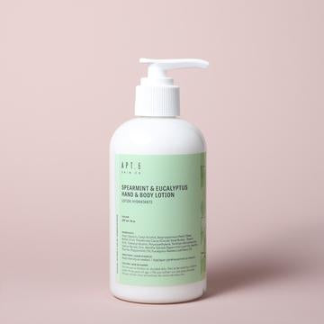 Canadian made spearmint eucalyptus hand and body lotion in a green bottle on a taupe background.