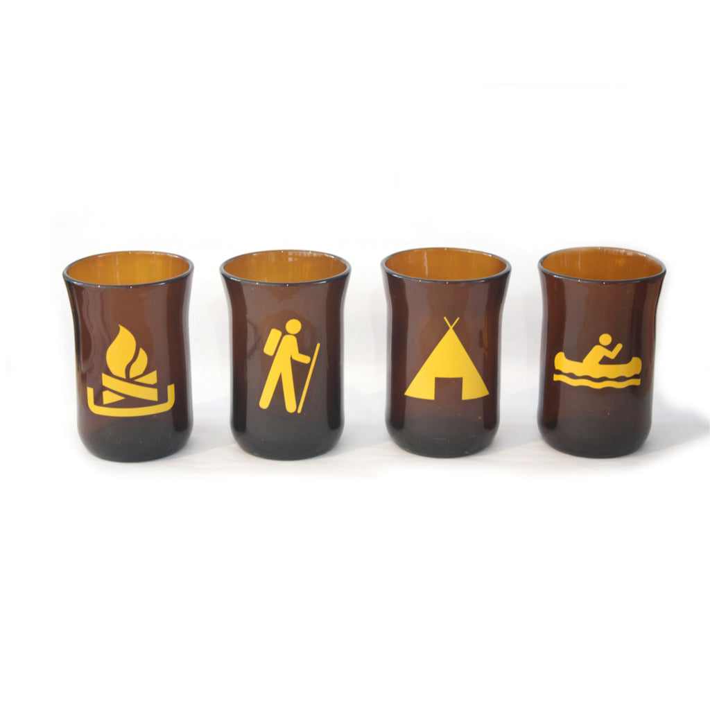 Made in Canada recycled beer bottle amber coloured tumbler glasses with yellow camping symbols of a tent, hiker, canoe and fire.