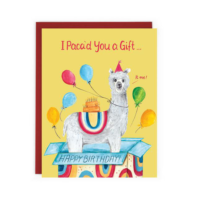 Hand drawn Made in Canada birthday card with an alpaca inside a present box, wearing a party hat, balloons and a cake on its back. Caption reads: I Paca'd You a Gift...It me!