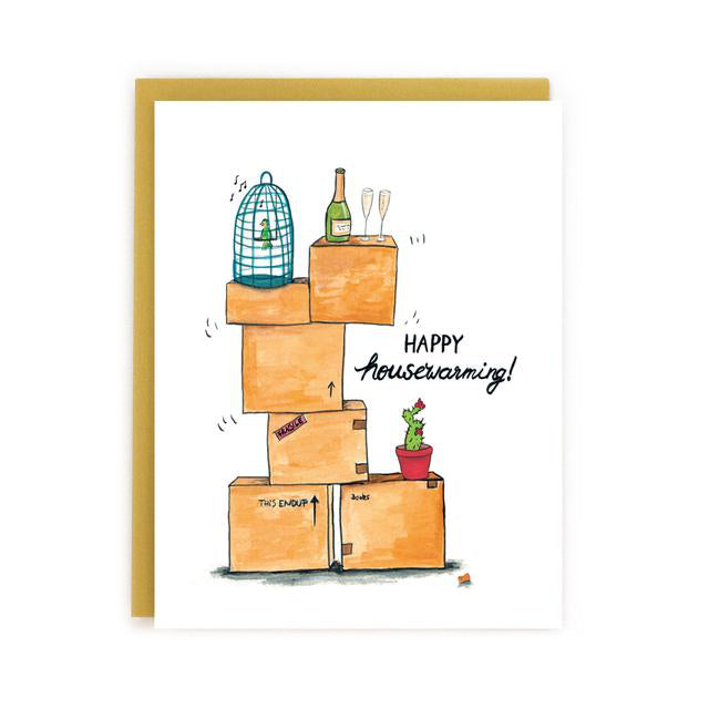 Made in Canada Housewarming greeting card with a drawing of a stack of boxes, a bird cage, a cactus and a bottle of champagne with two glasses. Caption reads: Happy Housewarming!