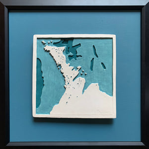 Canadian painted ceramic art featuring bathymetric view of the Bruce Peninsula in Ontario, Canada, with Lake Huron and Georgian Bay on either side. White ceramic set in black frame with blue mounting.
