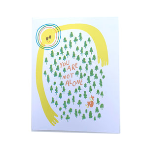 Made in Canada outdoor themed encouragement card, with silkscreen person in the forest being hugged by the Sun. Caption reads: You are not alone