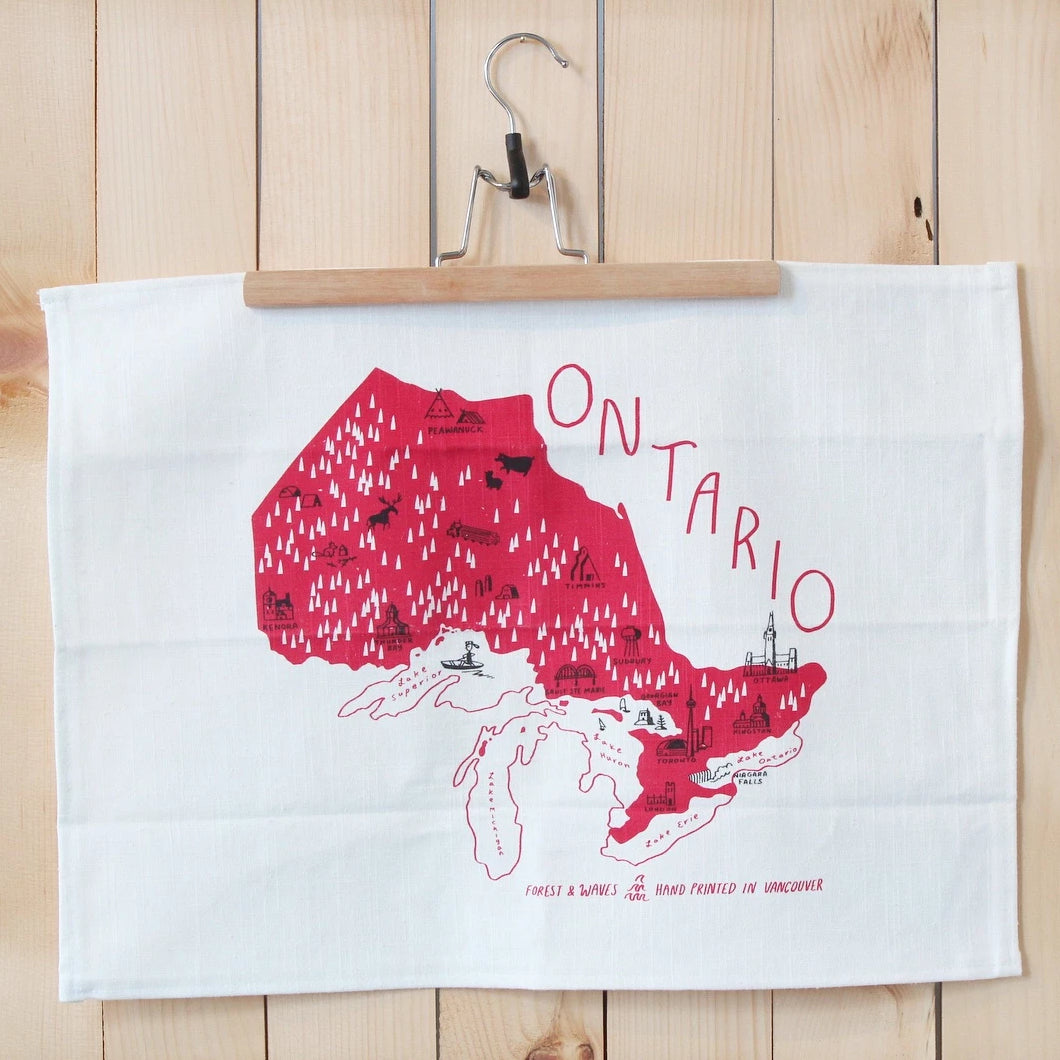 Made in Canada linen tea towel with red Ontario silkscreen print displayed as art on pine wood wall.