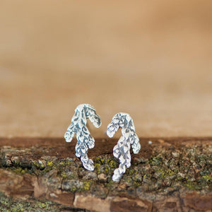 Made in Canada silver cedar leaf stud earrings displayed on mossy wood bark.