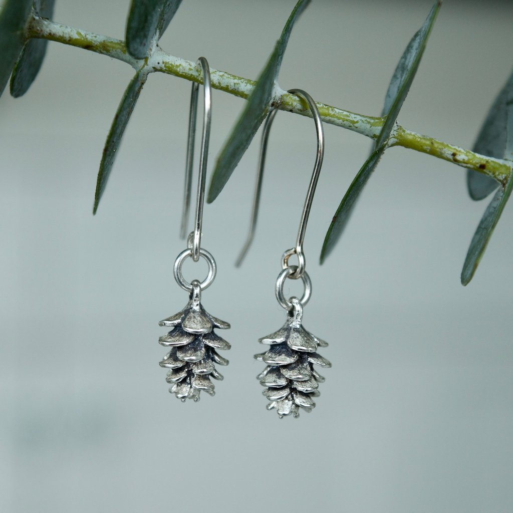 Made in Canada Justine Brooks silver pinecone drop earrings hanging on a fresh green eucalyptus sprig.