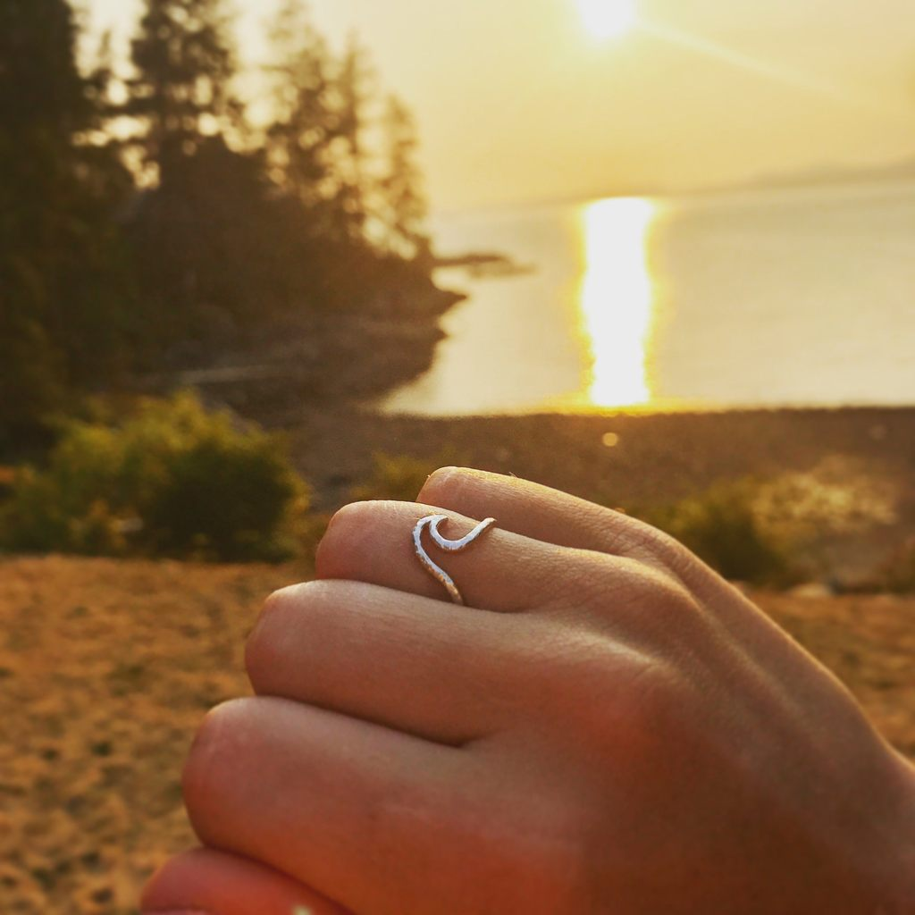 Made in Canada Justine Brooks silver textured wave ring with beach and sunset in the background.