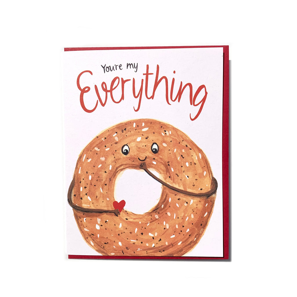 Canadian made love and friendship greeting card, with a silkscreen drawing of an everything bagel smiling and holding a heart. Caption reads: You're my everything