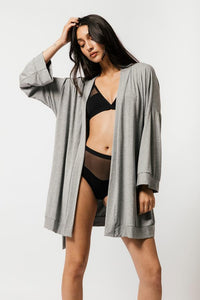Woman in black lingerie wearing grey Made in Canada bamboo robe over top.