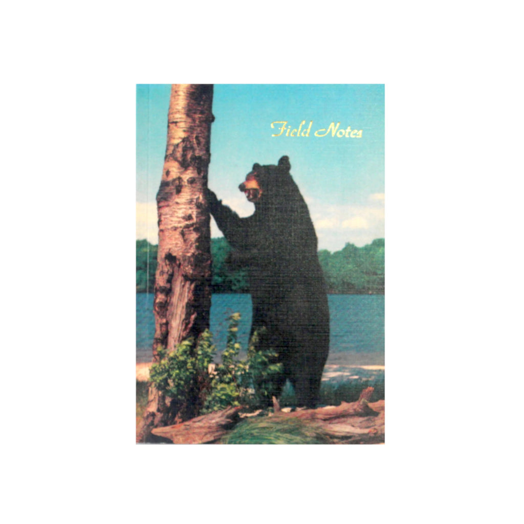Canadian made notebook with a printed photograph of a black bear clawing a birch tree by a lake.