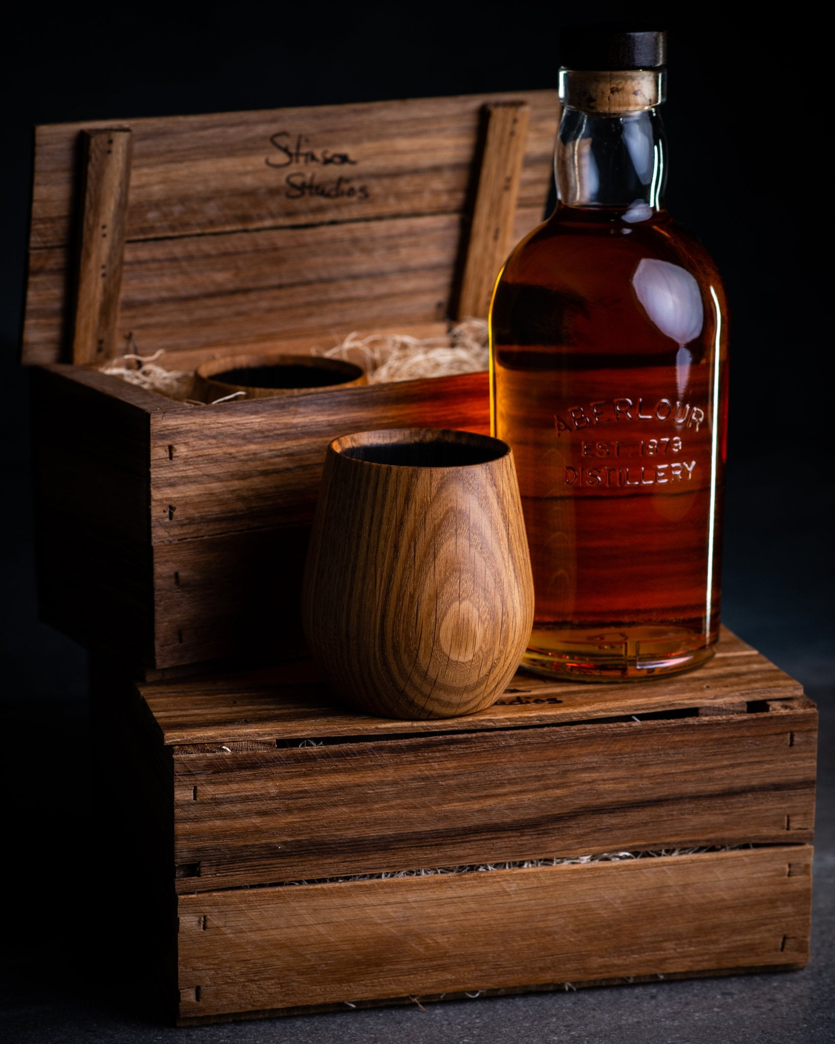 Made in Canada charred oak whiskey tumbler by Stinson Studios with gift crates and a bottle of whisky.