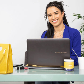 Fredi model, woman smiling while sitting at a desk on a computer