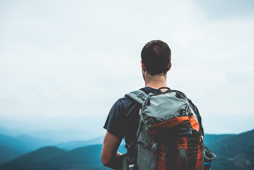 Man Standing on Top of a Mountain Wearing a Backpack