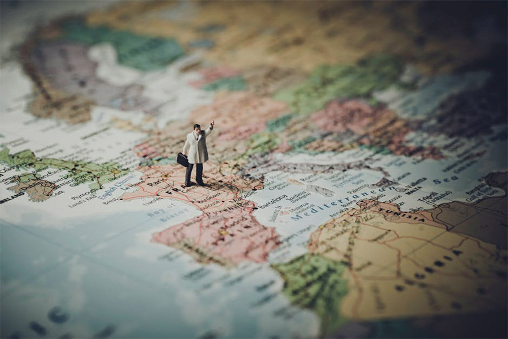 A toy person stood on top of a scratch off map of the world