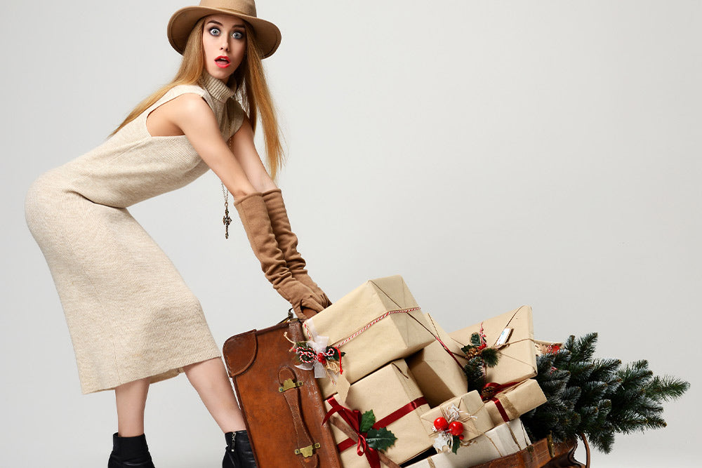 A well dressed woman pulling a basket full of presents