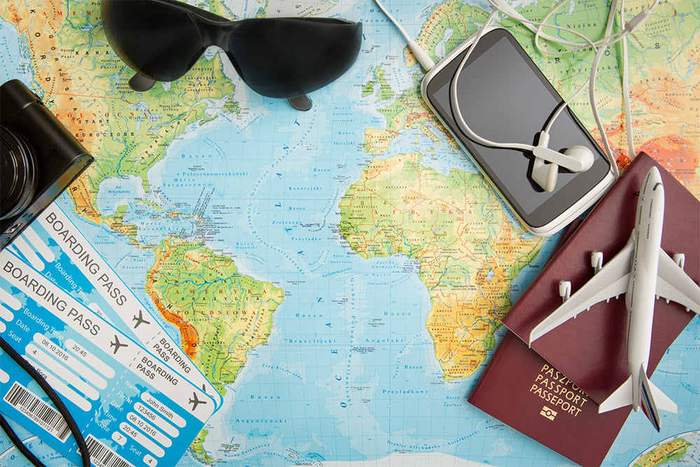 A world map with a passport, toy aeroplane, sunglasses, and other items on top
