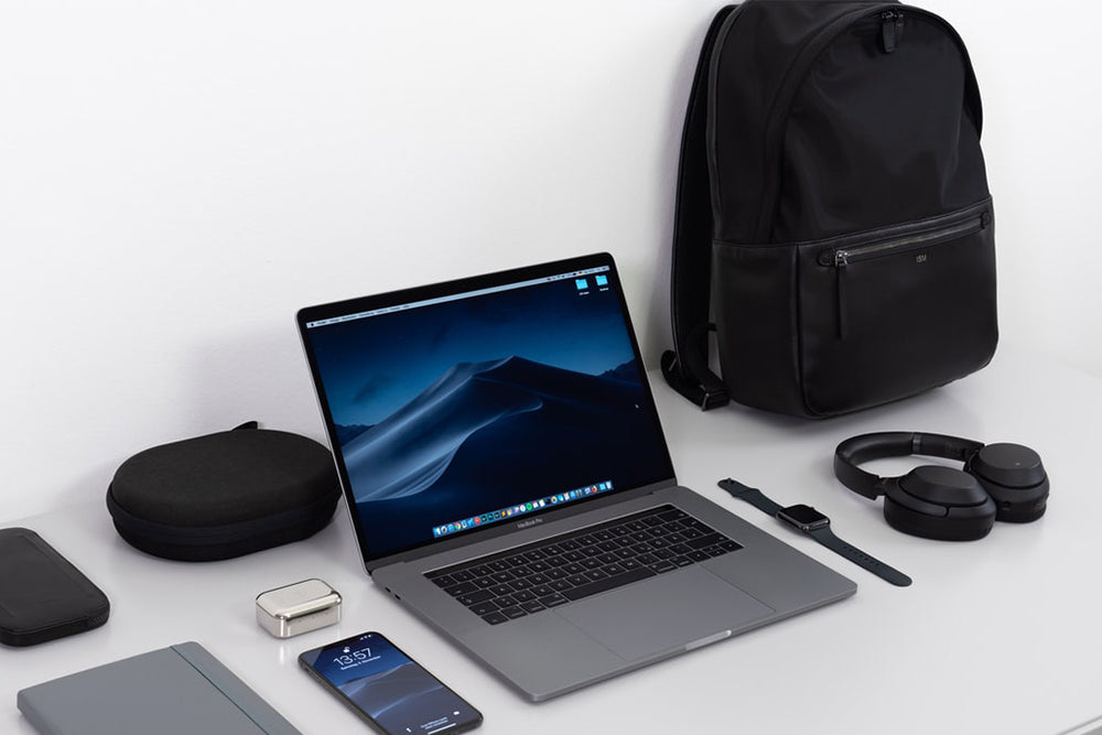 Laptop on a table surrounded by a backpack, mobile phone, and other items