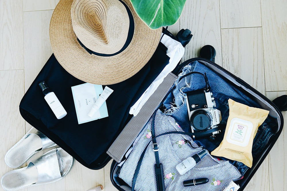 A travel suitcase filled with clothing, a sun hat, and other items