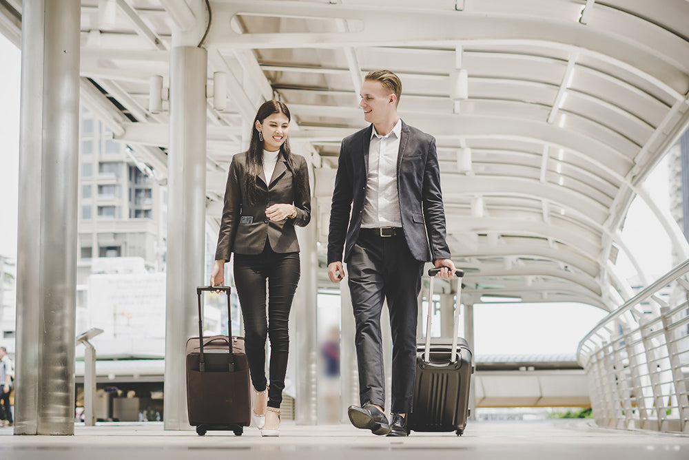 A man and a women in business wear walking in an airport with luggage