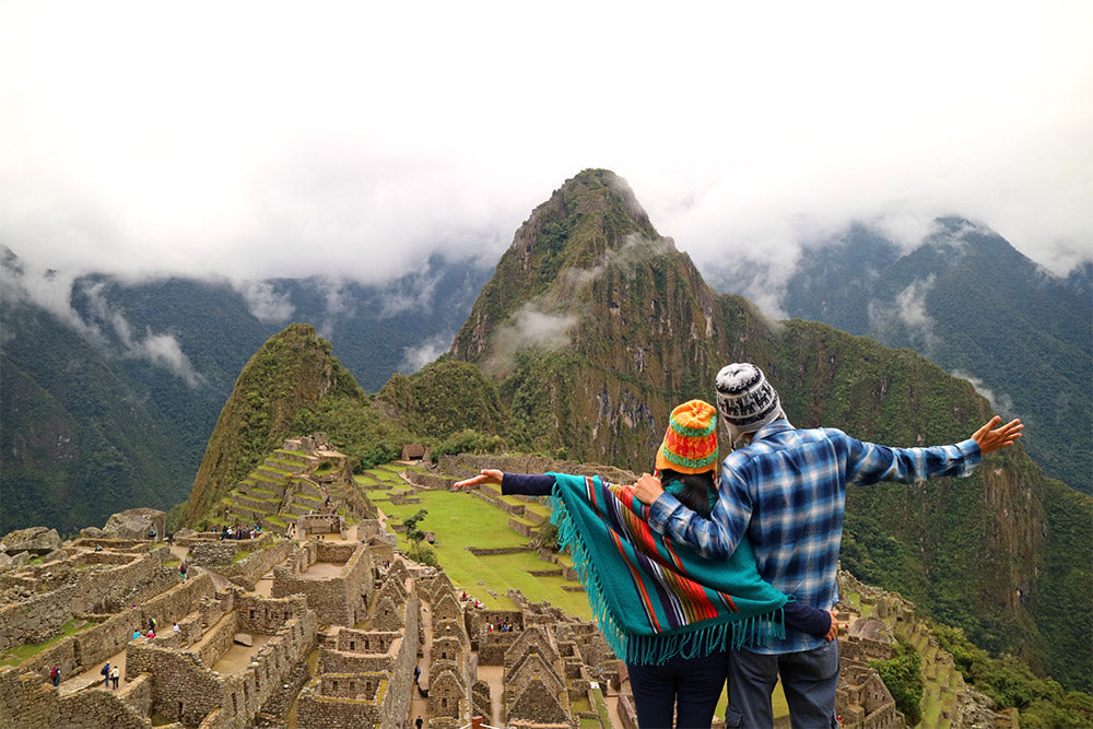 Two travellers stood on top of a mountain with their arms out stretched looking out at a beautiful landscape below
