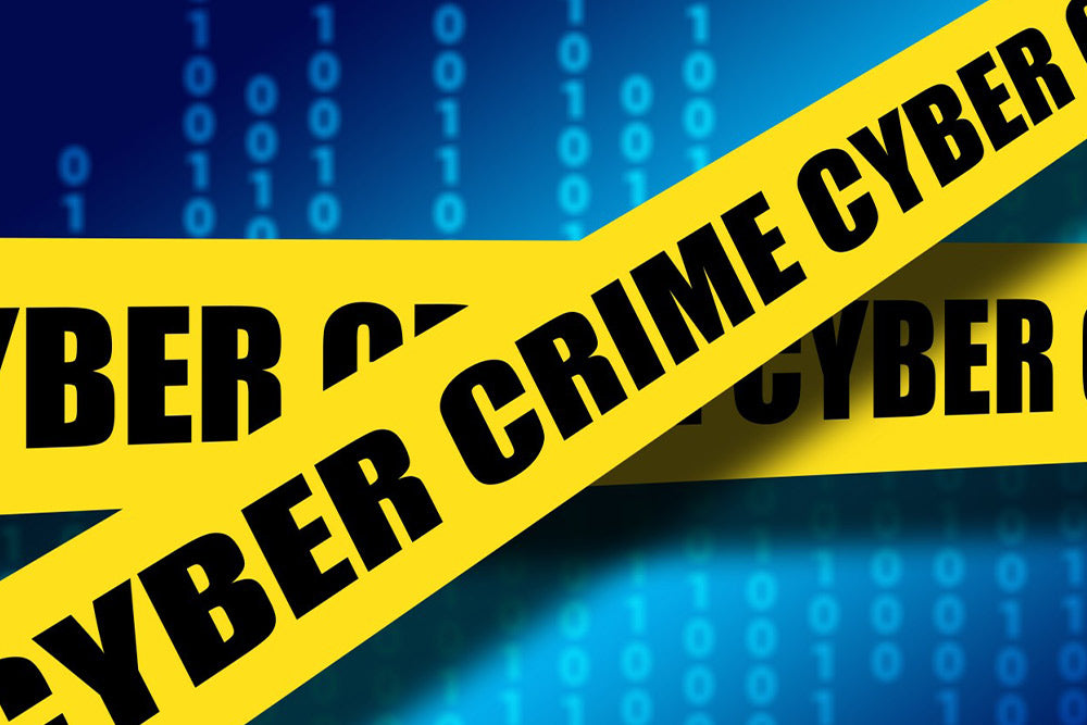"""Yellow police like tape with the words """"CYER CRIME"""" crossed over a blue background with computer code"""