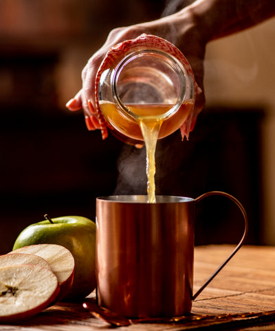 Hot cider poured on Blackberry Lemon Thyme Mixicles
