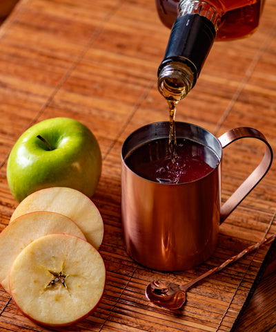 Bourbon poured into hot cider and Blackberry Lemon Thyme Mixicles