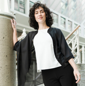 Photo of woman with black curly hair wearing a black see through cardigan in black with a white shirt, she is standing on a set of stairs in a building