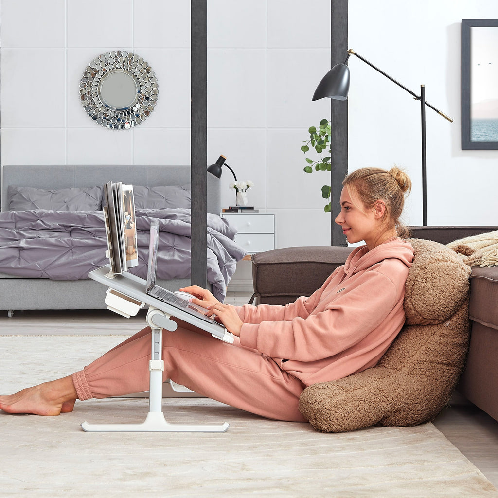 A Woman working on her laptop while sitting on the floor. She's using our portable laptop bed desk, Snug Desk and our backrest reading pillow with arms, Snug Pillow.