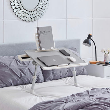 Snug Desk, a portable laptop desk on a bed, with a laptop, mouse, cellphone on its surface. Alongside a textbook in it's bookstand and pens in its side drawer.