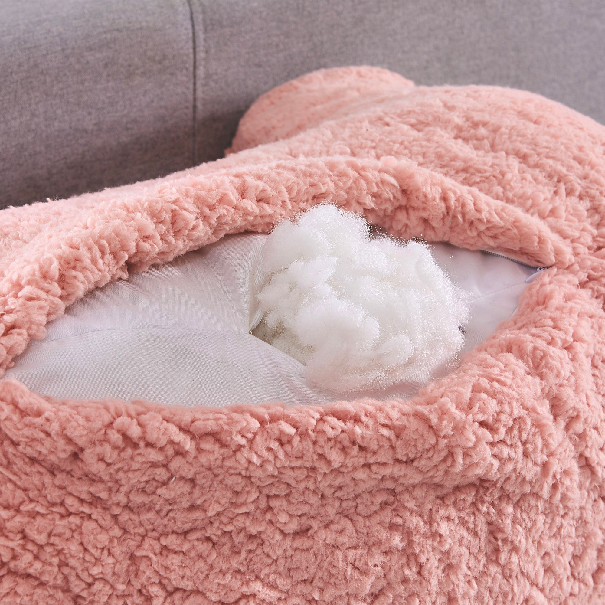 A closeup of the fleece inside a pink backrest reading pillow.