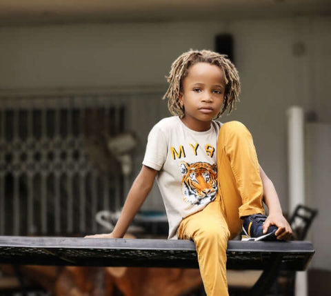 boy with dreads wearing tee shirt and chinos