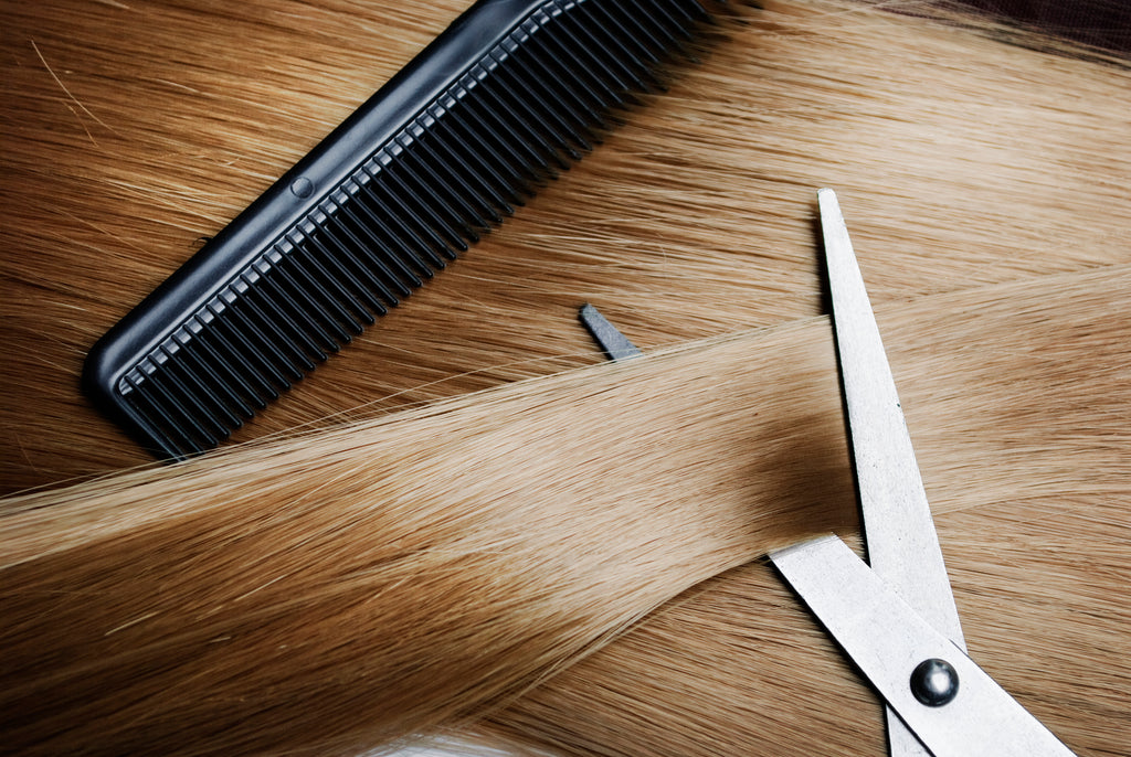 blond hair being combed and cut with scissors